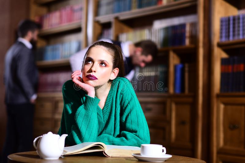 Woman in library read book at teapot drinking coffee from cup. literature cafe with cute girl and men. student life in. University. agile business and grammar royalty free stock image