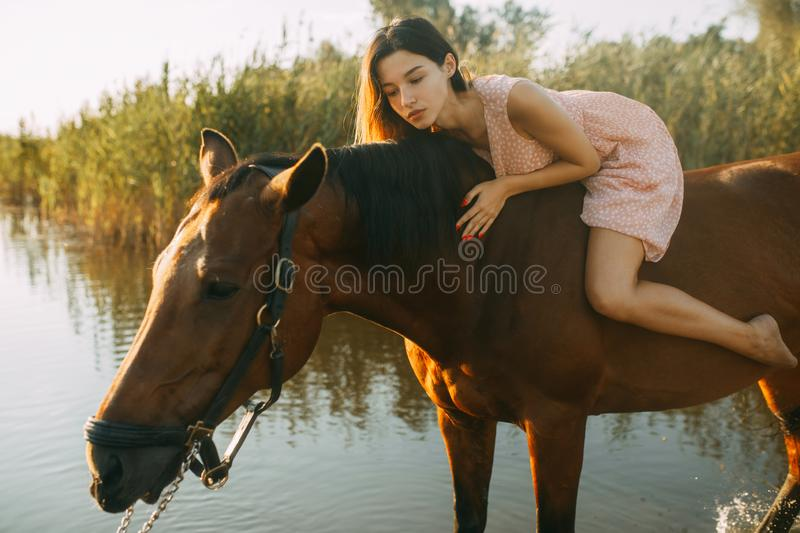 Woman lies astride a horse at river. A young woman lies astride a horse on background of river stock photography
