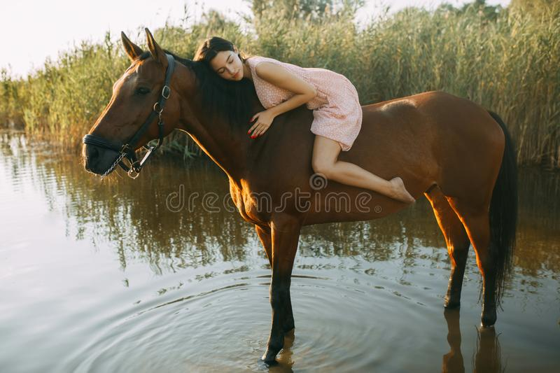 Woman lies astride a horse at river. A young woman lies astride a horse on background of river royalty free stock photo