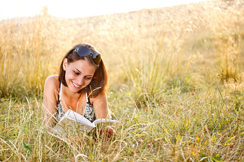 Woman lies on grass and reads book royalty free stock photo