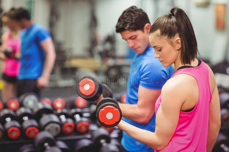 Woman lifting dumbbells with her trainer stock photo