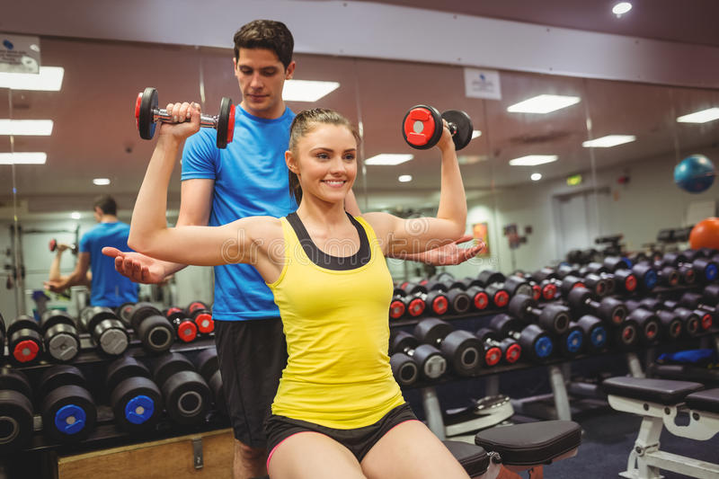 Woman lifting dumbbells with her trainer royalty free stock photography