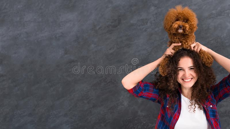 Woman lifting up her poodle dog up over her head royalty free stock photos