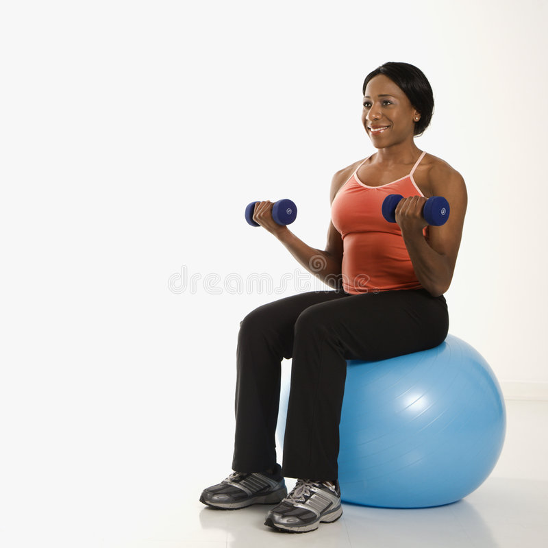 Woman lifting weights on ball. royalty free stock photos