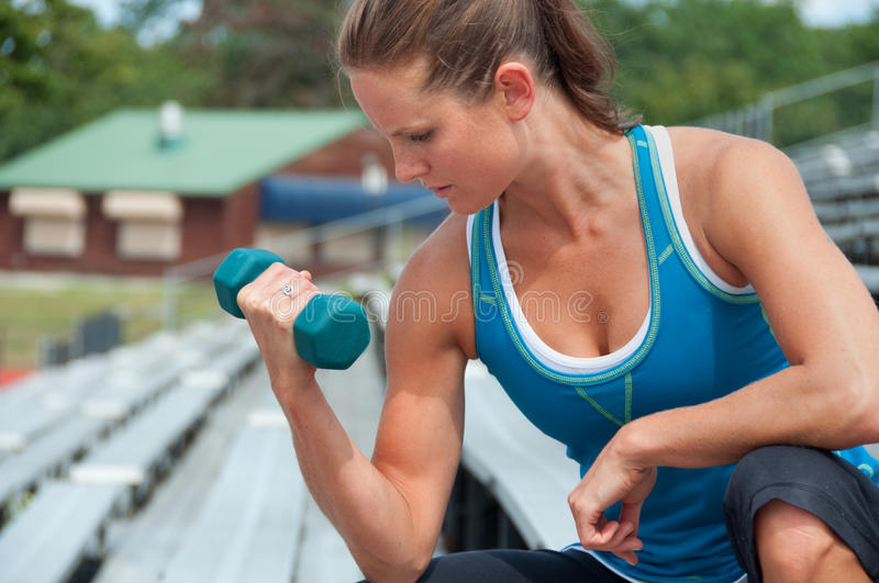Woman Lifting Weights on Bleachers at Outdoor Track. A woman does bicep curls with a dumbbell on the bleachers at an outdoor track stadium royalty free stock image
