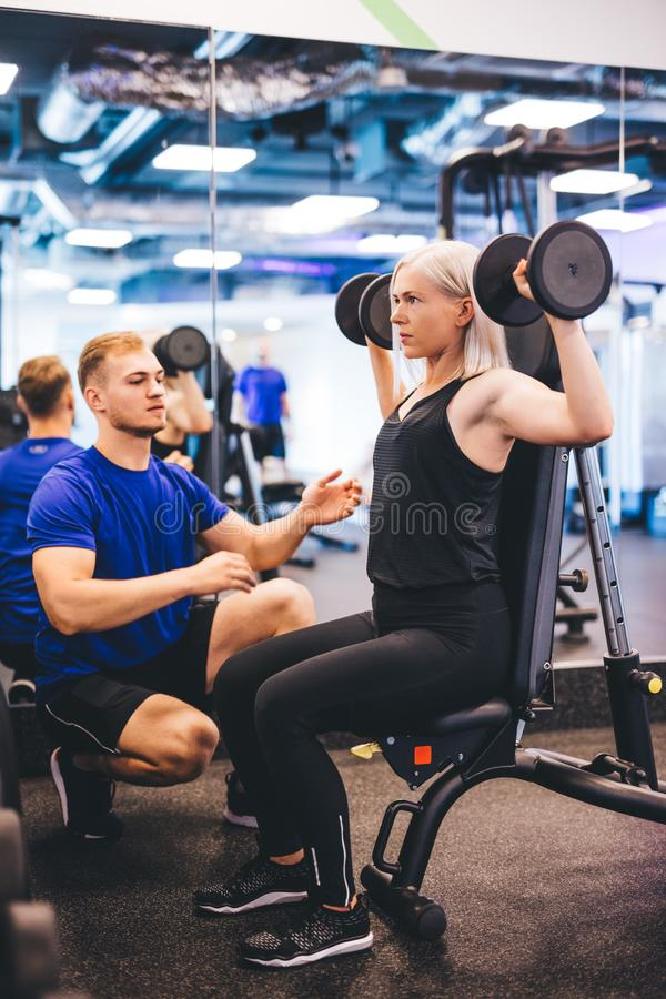 Woman lifting weights, exercising with personal trainer. stock photography