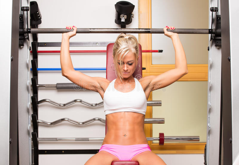 Woman lifts dumbbells in sport centre to develop muscles. In gym royalty free stock images