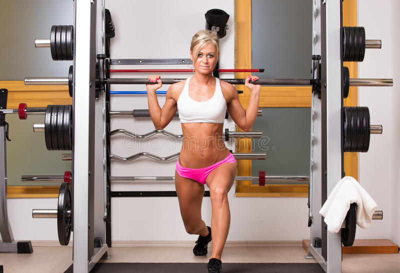 Woman lifts dumbbells in sport centre to develop muscles. In gym royalty free stock photography
