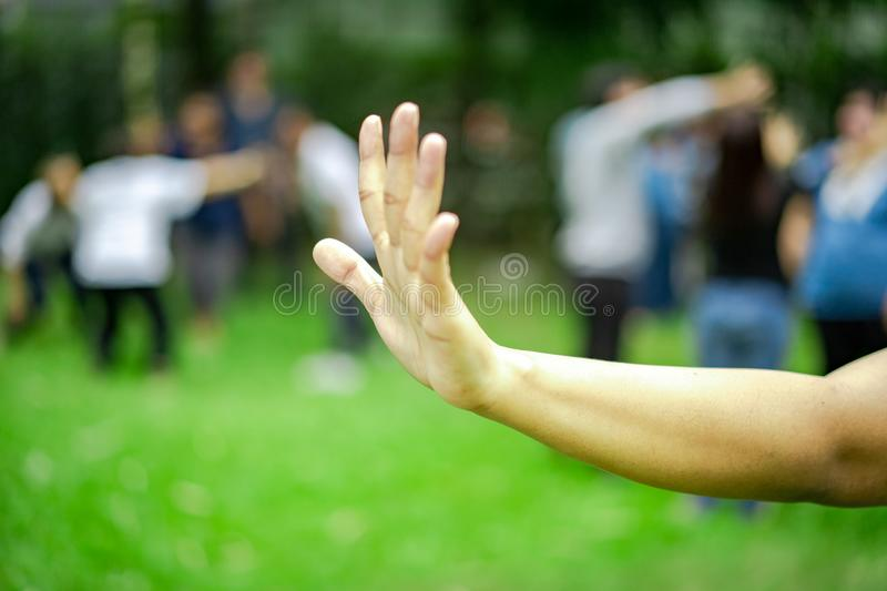 Woman lifts hand up and show five fingers of her hand in the garden, blur a lot of people in background stock photos