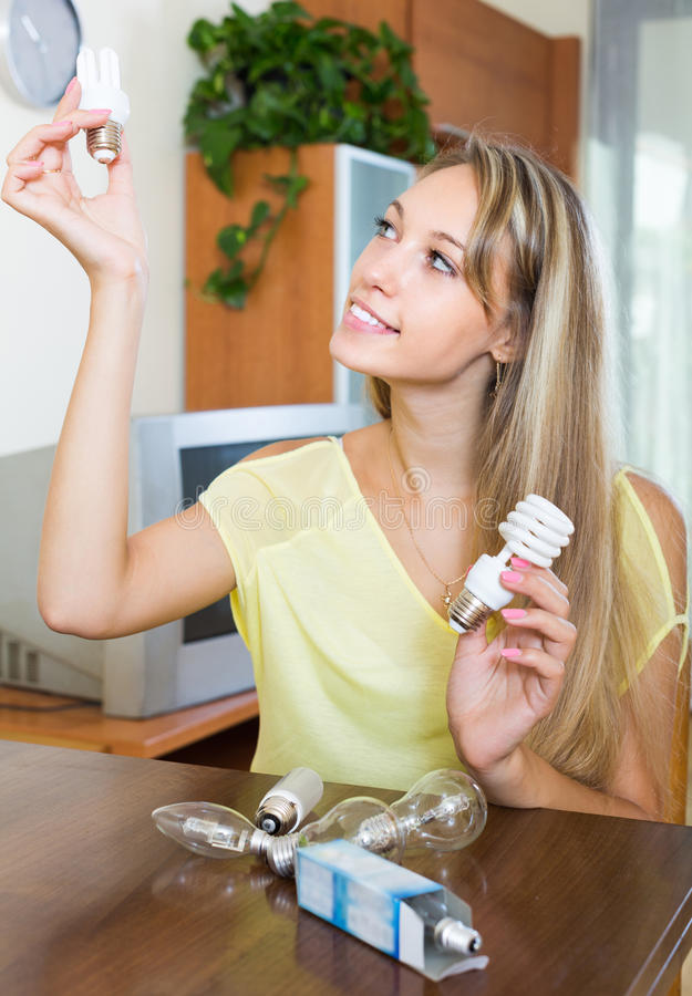 Woman with light bulbs at home stock photo
