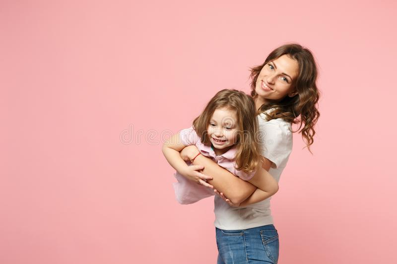 Woman in light clothes have fun with cute child baby girl. Mother, little kid daughter isolated on pastel pink wall royalty free stock photos