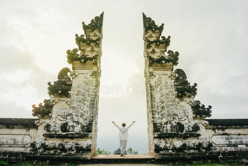 Woman in light clothes with her arms raised up symbolizes freedom. A woman in light clothes with her arms raised up symbolizes freedom. Ancient gates in pura royalty free stock image