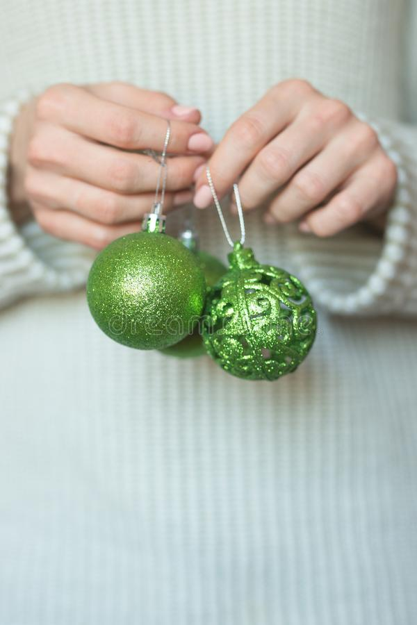 Woman in a light warm woolen sweater holding a toy green balls in her hands, copy space, selective focus. Christmas, new year holi. Day concept royalty free stock image