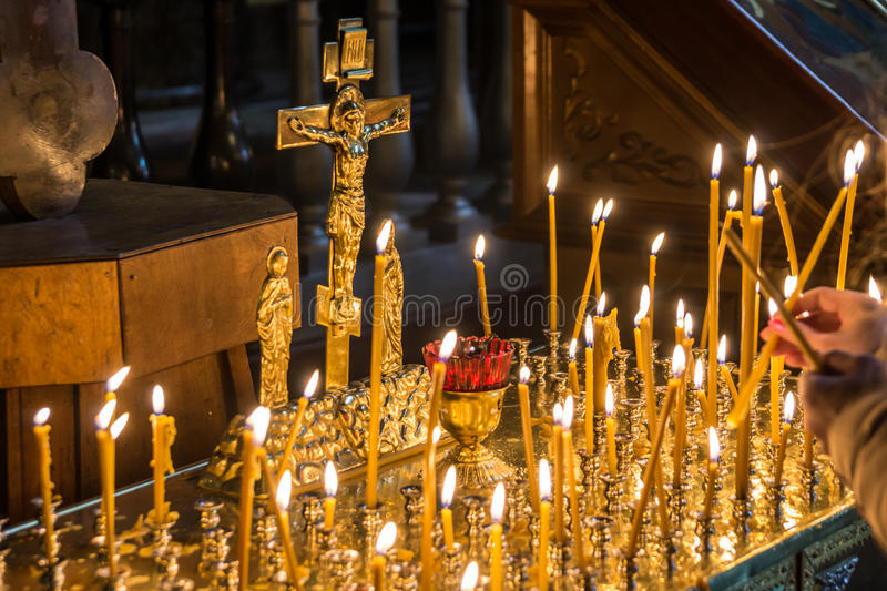 Woman lighting candles in christian church royalty free stock photography