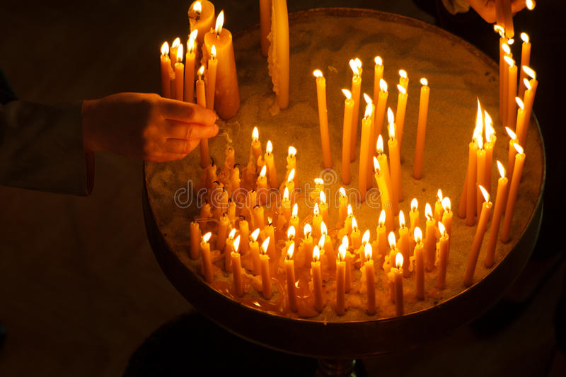 Woman lighting candles in a church stock photography