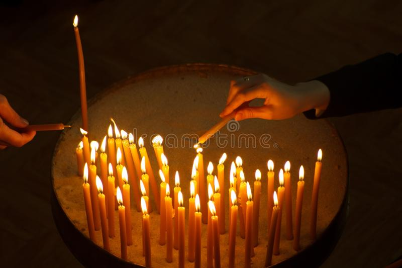 Woman lighting candles in a church royalty free stock photo