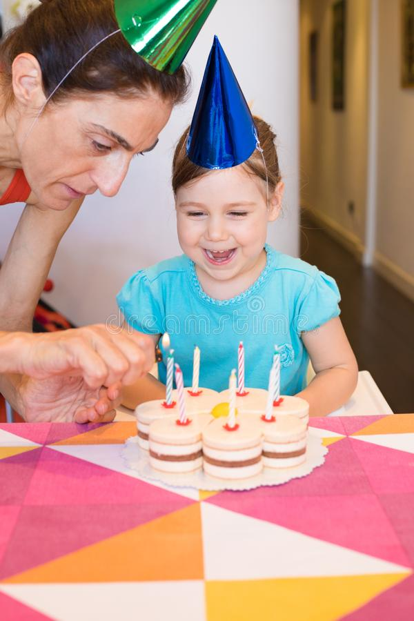 Woman lighting candles on birthday cake and child smiling stock images