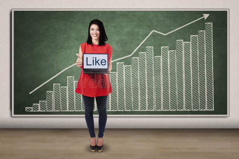 Woman with like text and financial chart. Successful woman showing a like text on laptop while giving thumb up in front of financial chart stock photos