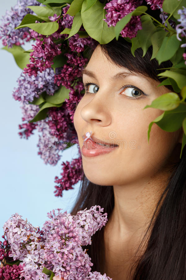 Woman with lilac bouquet and wreath as flowers hair style stock photo