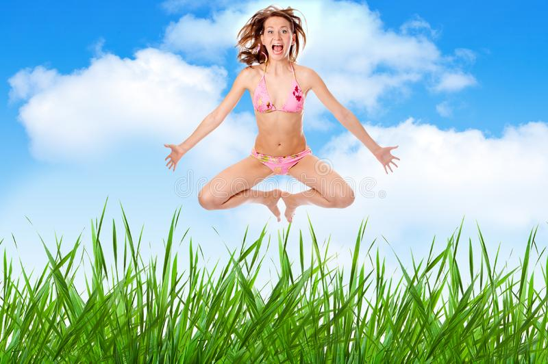 Woman in lingerie jump over grass royalty free stock photo