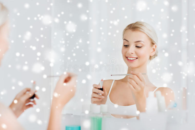 Woman with lipstick applying make up at bathroom. Beauty, make up, cosmetics, morning and people concept - smiling young woman with lipstick and applicator at stock images