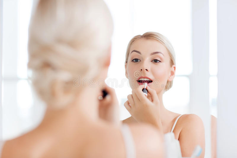 Woman with lipstick applying make up at bathroom royalty free stock photos