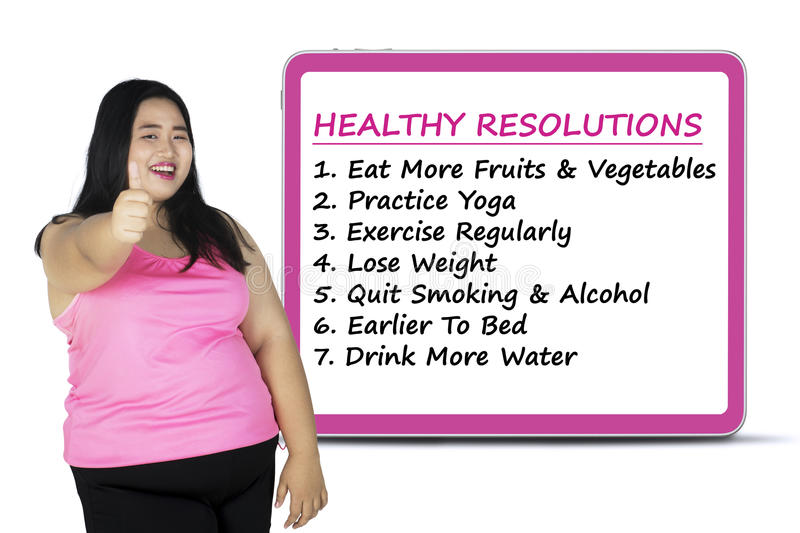 Woman with a list of healthy resolutions. Image of overweight woman showing thumb up with a list of healthy resolutions on the board royalty free stock photography