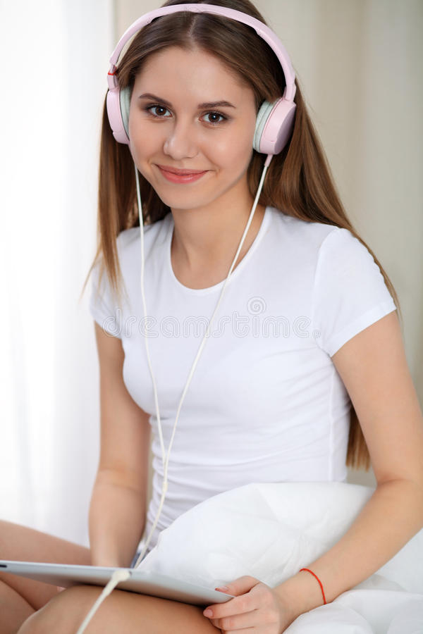 Woman listening music in bed with pink headphones after wake up, entering a day happy and relaxed after good night sleep royalty free stock photos