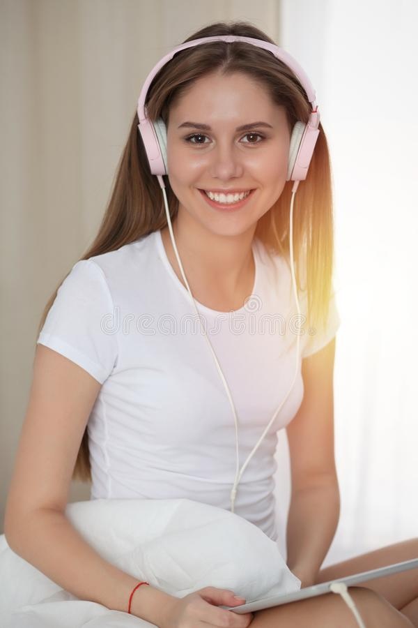 Woman listening music in bed with pink headphones after wake up, entering a day happy and relaxed after good night sleep stock photos
