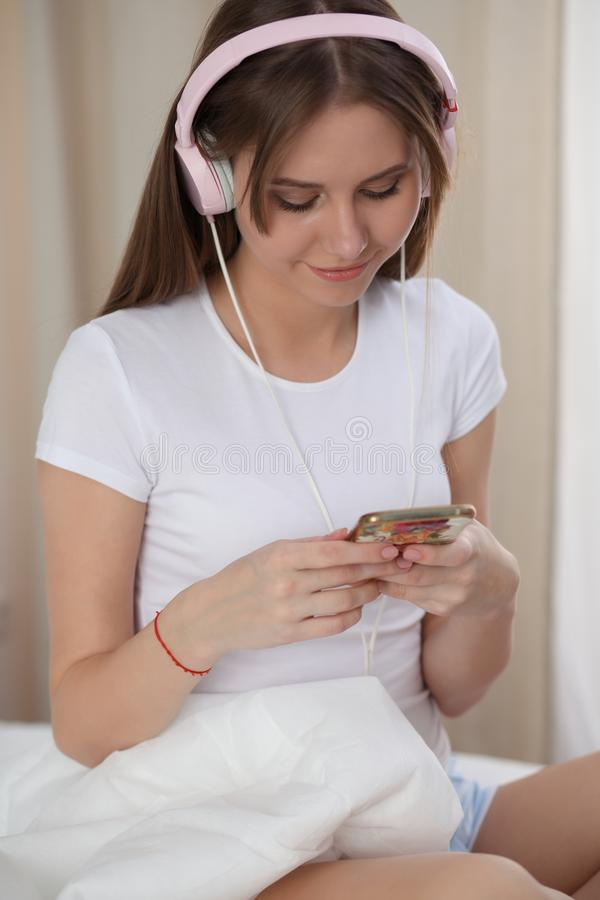 Woman listening music in bed with pink headphones after wake up, entering a day happy and relaxed after good night sleep stock image