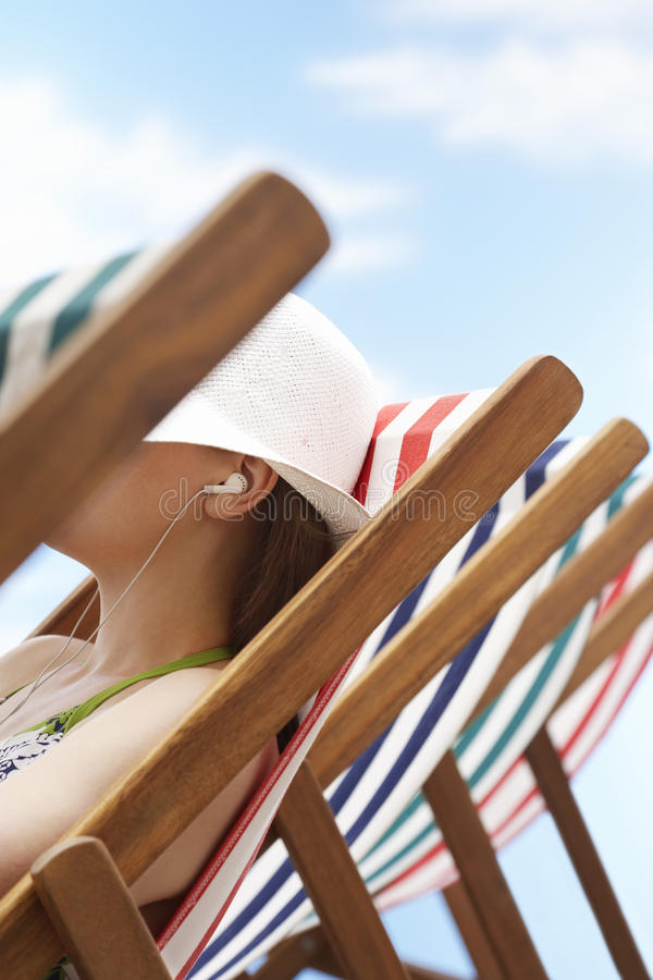 Woman Listening Music Through Earphones On Deckchair. Closeup of woman listening music through earphones on deckchair at beach stock photos