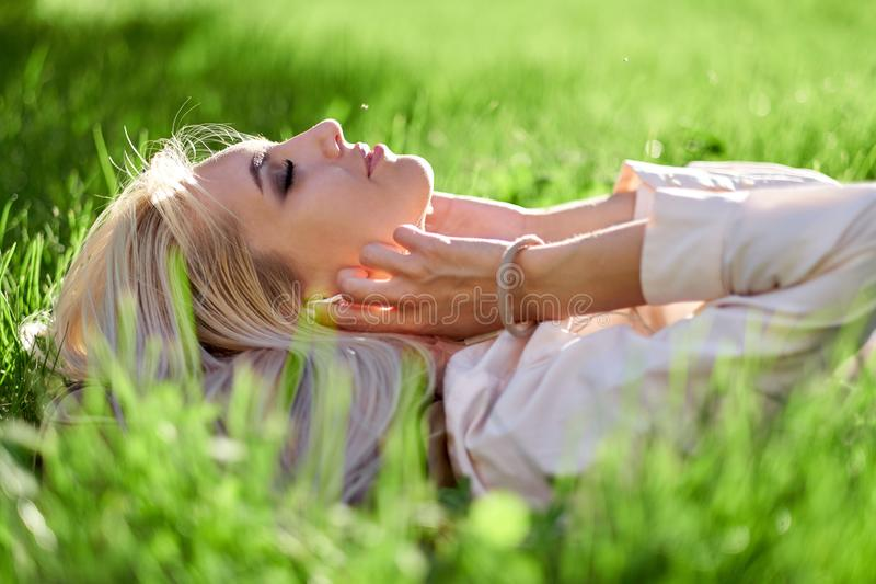 Woman closed her eyes and listening music with her headphones and lying in meadow. Enjoys music, relaxes royalty free stock photos