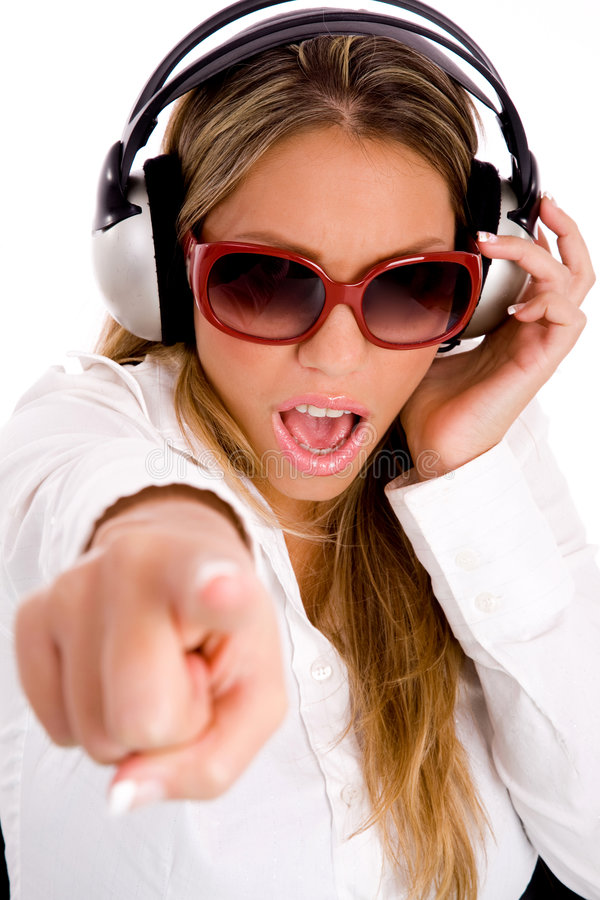 Woman listening music and pointing at camera stock image
