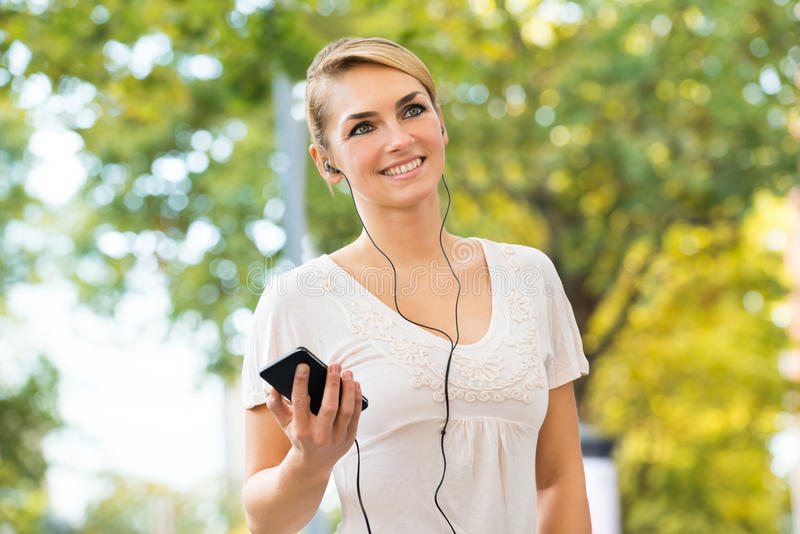 Woman Listening To Music Through Headphones Using Mobile Phone royalty free stock images
