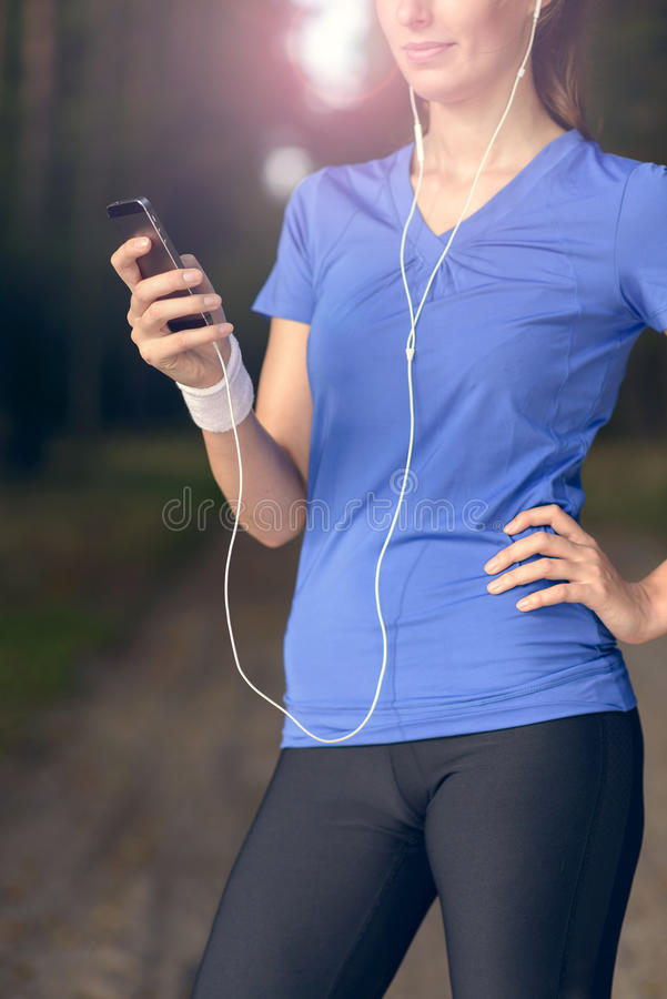Woman listening to music on an MP3 player stock photo