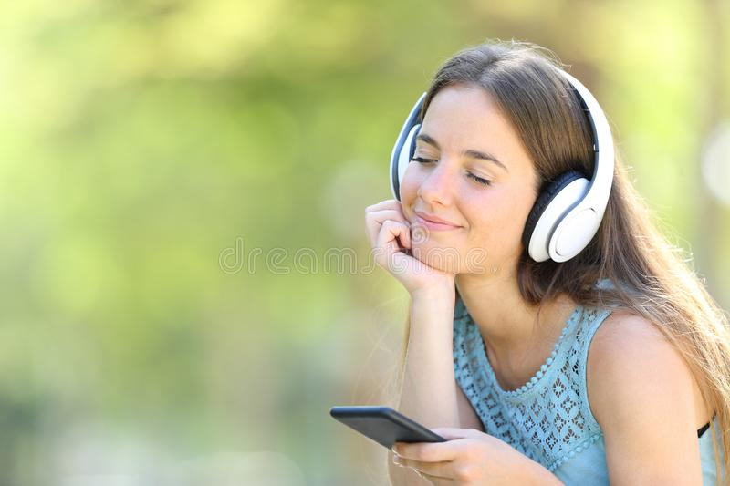 Woman listening to music with smart phone relaxing on green. Woman listening to music with a smart phone relaxing in a park with a green background royalty free stock images