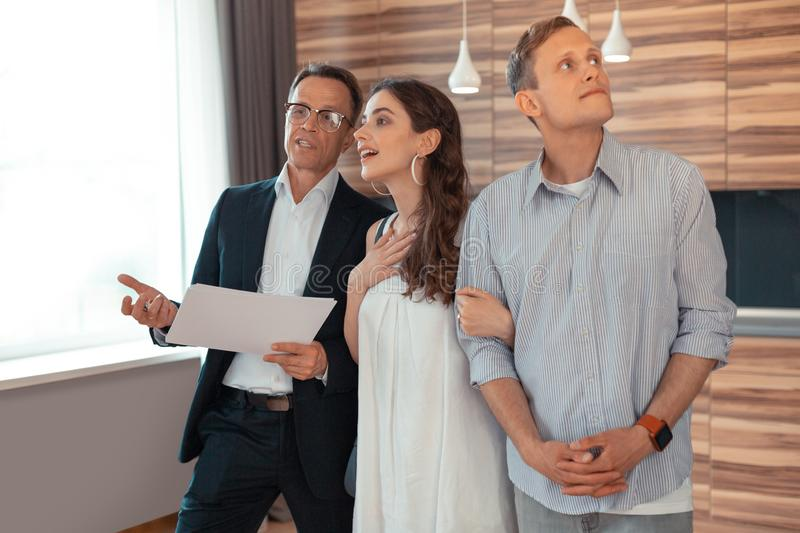 Woman listening to realtor while standing near husband stock photos