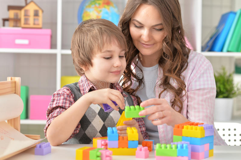 Woman and little boy playing lego stock photos