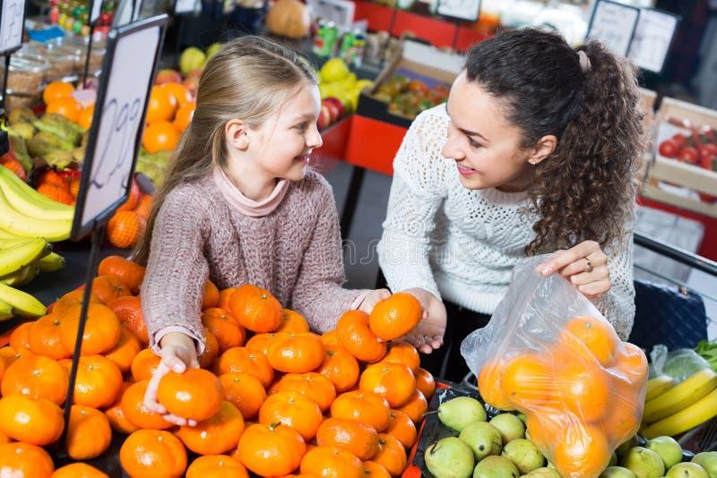 Woman and little girl buying fruits. Joyful smiling young women and little girl choosing fruits at market stock photo