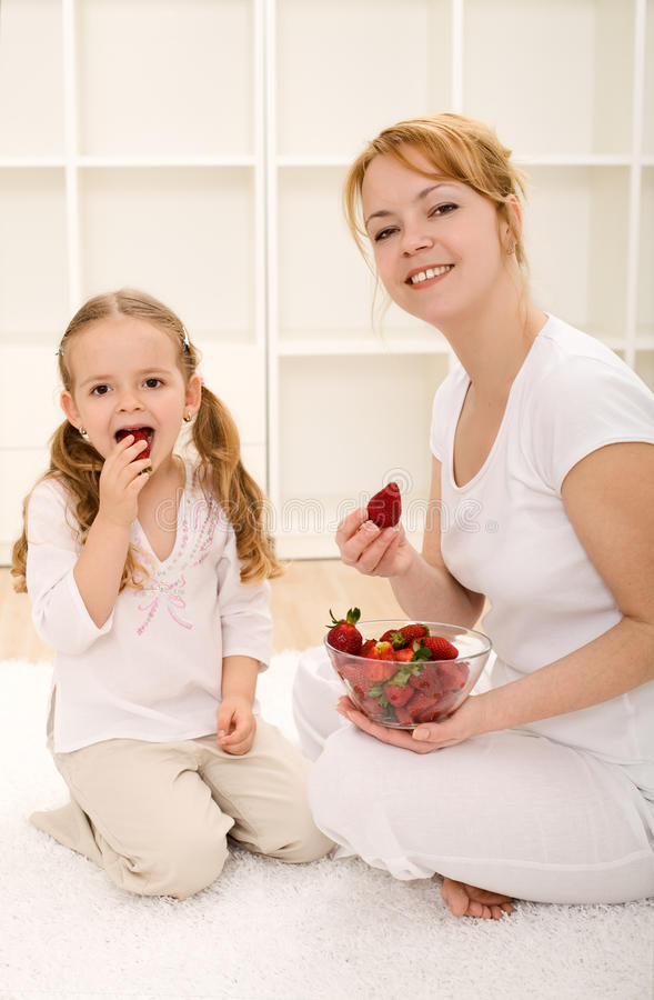 Woman and little girl eating fresh strawberries royalty free stock photo