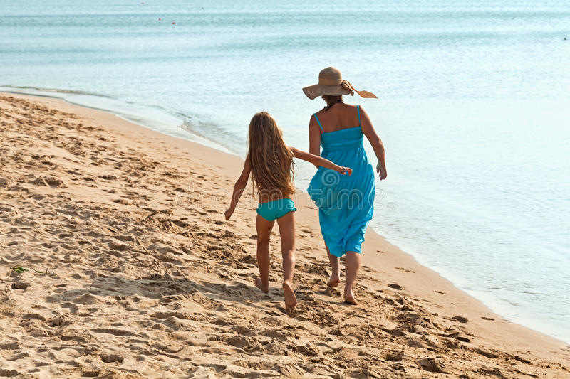 Woman and little girl on a morning walk by the sea stock images