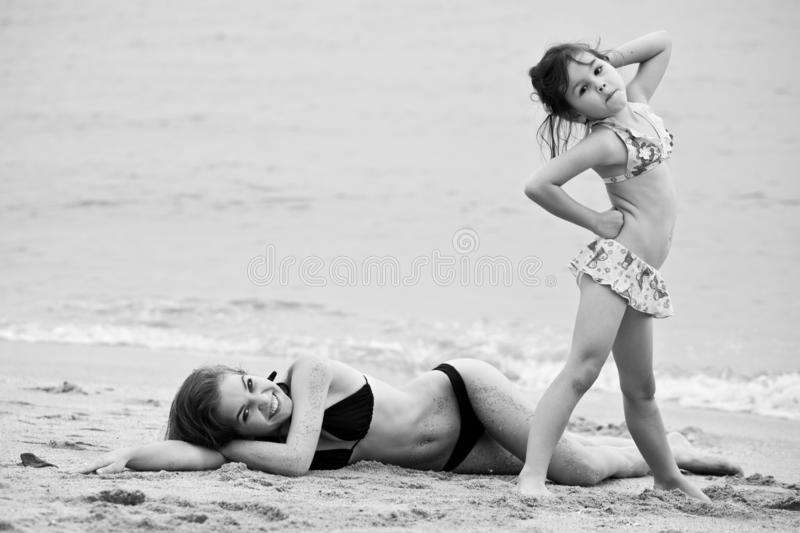 Woman and little girl relaxing on the beach stock photo