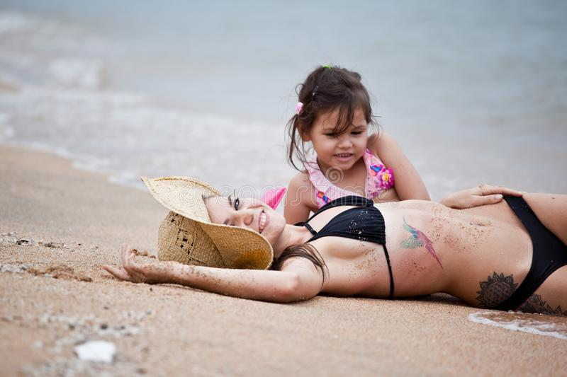 Woman and little girl relaxing on the beach stock image