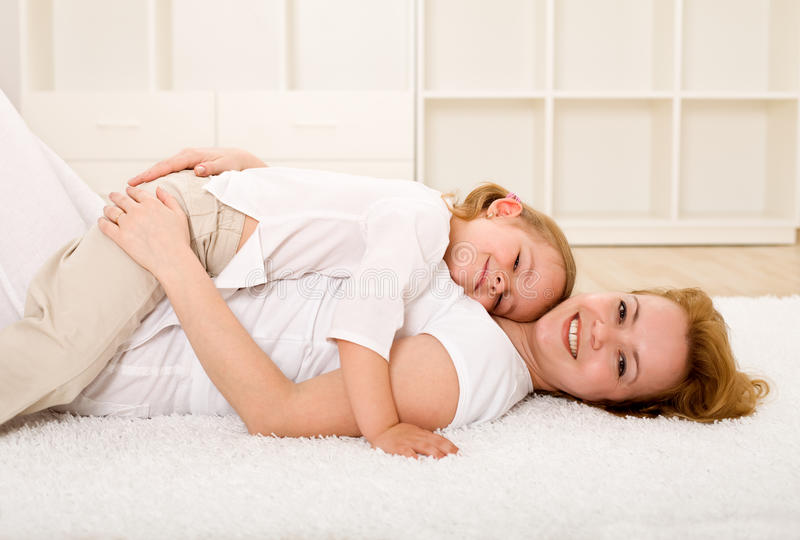 Woman and little girl relaxing on the floor stock photos