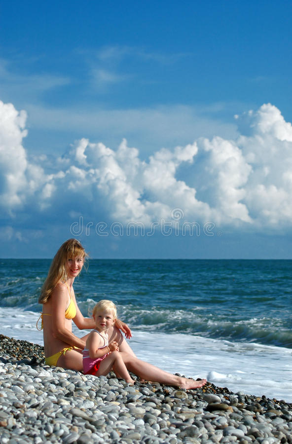 Download Woman And Little Girl Sit On Seacoast Stock Photo - Image: 10448072