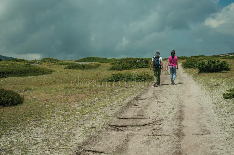 Woman and little girl walking in a trail on highlands royalty free stock image