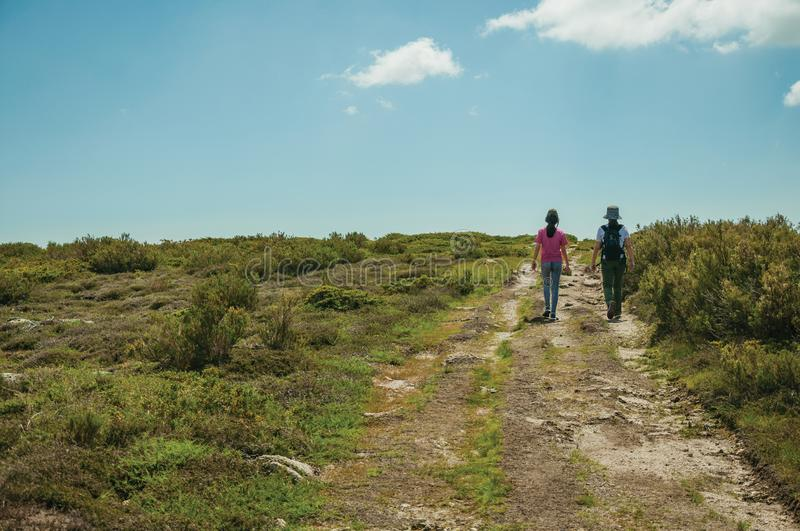 Woman and little girl walking in a trail on highlands stock image