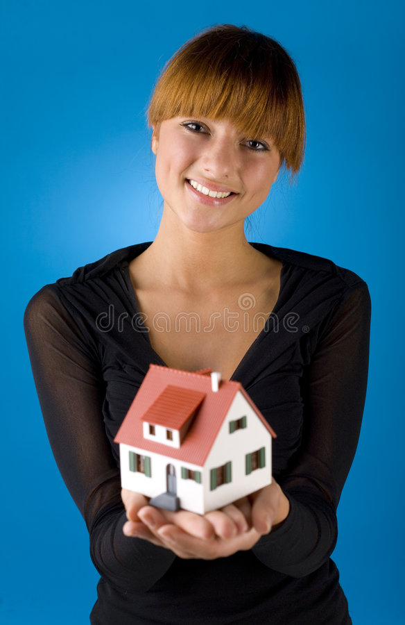 Woman with little house. Beautiful woman with house miniature in hands. Smiling and looking at camera. Blue background, front view stock photography