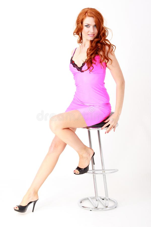 Woman in little pink dress sitting on chair stock photo