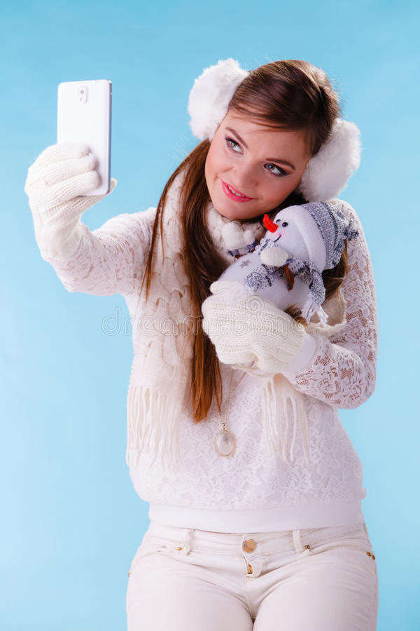 Woman with little snowman taking selfie photo. Pretty cute woman holding little snowman taking selfie self photo picture with camera. Attractive girl in stock photo